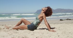Side view of young African american woman relaxing on the beach 4k stock footage