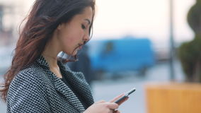 Side-view of the young amazing dark brown-haired girl in strict gray jacket and black dressstaying communicating with stock video