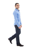 Side view of young arabic bearded business man in blue shirt wal Royalty Free Stock Image