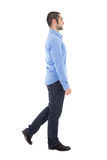 Side view of young arabic business man in blue shirt walking iso Royalty Free Stock Photography