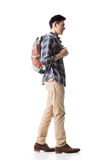 Side view of young Asian backpacker. Full length portrait isolated on white background Stock Photo