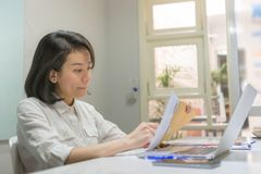 Side view of young Asian businesswoman reading financial report royalty free stock image