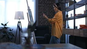 Smiling female painter photographing new artwork. Side view of young asian woman artist taking a picture of her masterpiece at easel on cellphone in domestic art stock footage