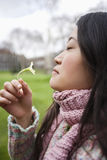 Side view of a young Asian woman smelling flower in park Royalty Free Stock Images