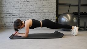 Side view of young athletic caucasian woman in sports clothing keeping plank position while exercising indoors in gym stock video