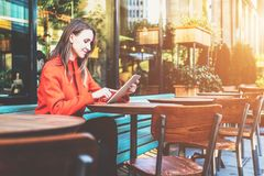 Side view. Young attractive woman in orange coat is sitting outside in cafe at table and uses tablet computer. stock images