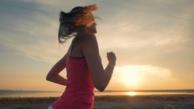 Side view of a young attractive woman running during sunset. Healthy lifestyle concept. stock footage