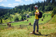 Young bearded man admiring view of mountains. Side view of young bearded man admiring view of mountains. Looking at beautiful mountains inspirational landscape Royalty Free Stock Photos