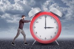Side view of young bearded man in casual clothes pushing big red alarm clock, standing outside under gray cloudy sky. stock images