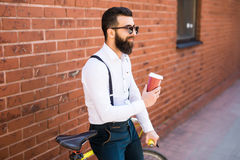 Side view of young bearded man drinking coffee while sitting on his bicycle outdoors Stock Photography