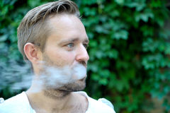 Side view of young bearded man is smoking. Against freen leaf Stock Image