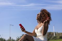 Side view of a young beautiful curly afro woman sitting on ground in a park and using a mobile phone while smiling in a sunny day stock image