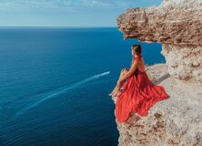 Side view a Young beautiful sensual woman in a red long dress posing on a rock high above the sea during sunrise. Girl. On the nature on blue sky background