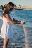 Side view of a young beautiful slender girl with a flat belly and a round booty admiring the blue ocean standing on the. A young, slender girl stands on the royalty free stock photo