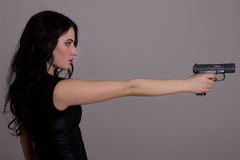 Side view of young beautiful woman with gun over grey Stock Photography