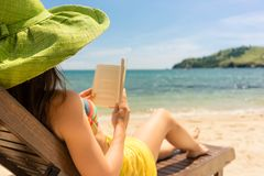 Young beautiful woman reading a book at the beach in a sunny day. Side view of a young beautiful woman reading a book while sitting on a wooden lounge chair at Stock Photography