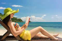 Young beautiful woman reading a book at the beach in a sunny day. Side view of a young beautiful woman reading a book while sitting on a wooden lounge chair at Royalty Free Stock Photography