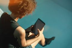 Brazilian girl with digital pad next to swimming pool royalty free stock images