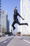 Side view young black man wearing casual clothes jumping in urban background. Lifestyle concept. Millennial african guy wearing. Side view of a young black man royalty free stock photo
