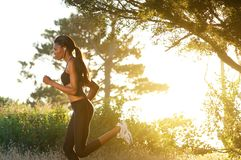 Side view young black woman running in nature Stock Photo