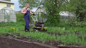 Young blond muscular farmer cultivates ground soil with rotary mini tiller. Side view of young blond muscular farmer cultivates ground soil with rotary mini stock video footage