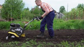 Young blond muscular farmer cultivates ground soil with rotary mini tiller. Side view of young blond muscular farmer cultivates ground soil with rotary mini stock video