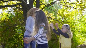 Side view of young blonde woman staying in the sunny park and blowing soap bubbles. Her two little pretty daughters. Running around trying to catch bubbles stock footage