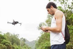 Side view of a young boy learning to fly a drone in outdoors stock photo