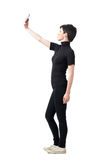 Side view of young brunette in black clothes taking selfie from high angle Stock Image