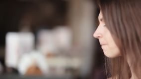 Side view of young brunette woman drinking coffee. Woman has a cup of coffee. Close-up stock footage