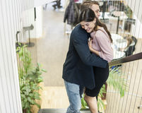 Side view of young business couple hugging on staircase Royalty Free Stock Images
