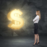 Side view of young business lady who is looking at the huge golden dollar sign. Stock Photos