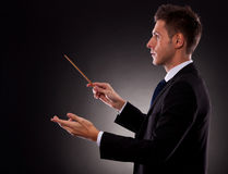 Side view of a young business man directing. With a conductor's baton stock image