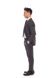 Side view of a young business man standing in line Royalty Free Stock Images