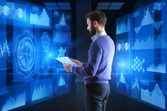Finance and analytics concept. Side view of young businessman analyzing contract in interior with glowing business hologram. Finance and analytics concept. 3D Stock Photography