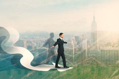 Leadership and economy concept. Side view of young businessman balancing on arrow. Abstract city background with forex chart. Leadership and economy concept stock photography