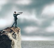 Research and success concept. Side view of young businessman on cliff using binoculars to look into the distance. Sky and clouds background. Research and success stock photography