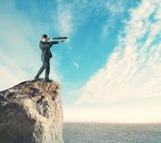 Research and vision concept. Side view of young businessman on cliff using binoculars to look into the distance. Sky and clouds background. Research and vision royalty free stock photo