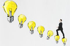 Idea concept. Side view of young businessman climbing drawn light bulbs on white background. Idea concept Stock Image