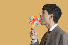 Side view of young businessman licking lollipop over colored background Royalty Free Stock Photo
