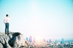 Businessman looking at city. E view of young businessman looking into the distance on cliff with city skyline, copy space and sunlight. Research and vision royalty free stock photo