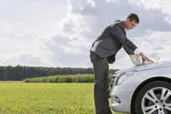 Side view of young businessman looking at map on car hood at countryside Stock Images