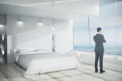 Research concept. Side view of young businessman looking out of window in modern bedroom interior with white furniture, wooden floor and panoramic view. Research Royalty Free Stock Photo