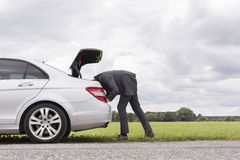 Side view of young businessman looking in trunk of car at countryside Royalty Free Stock Image