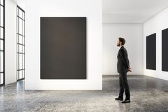 Man looking at blank poster. Side view of young businessman in modern concrete room interior with city view, looking at blank poster. Gallery, exhibition Stock Photography