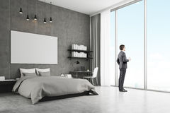 Side view of a young businessman near his bedroom window. Side view of a young businessman in suit standing in his bedroom and holding a paper cup of coffee Royalty Free Stock Photo