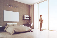 Side view of a young businessman near his bedroom window, toned. Side view of a young businessman in suit standing in his bedroom and holding a paper cup of Stock Photo