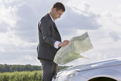 Side view of young businessman reading map by car at countryside Stock Image