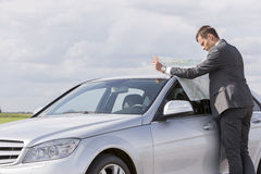 Side view of young businessman reading map by car at countryside Stock Photos