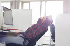 Side view of young businessman relaxing at computer desk in office Royalty Free Stock Photo